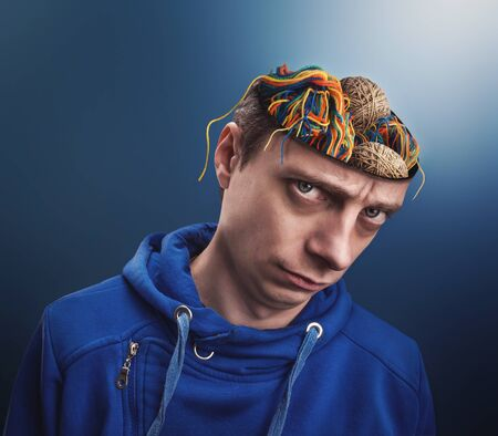 odd jobs: Young man with balls of yarns instead of his brain