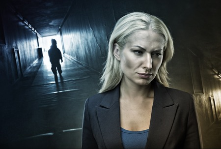 lonelyness: Frustrated blond woman stands in the dark corridor