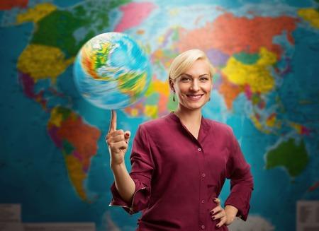 Mujer agente de viajes con un globo contra un mapa del mundo