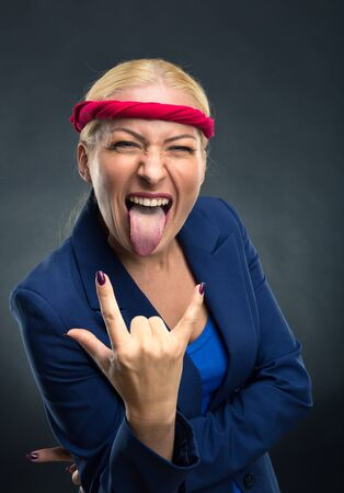 heavy metal: Cool businesswoman showing heavy metal hand gesture over gray background