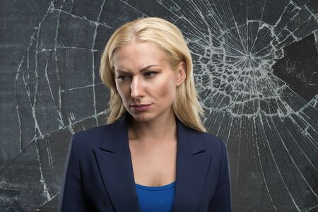 lonelyness: Sad woman stands against broken glass