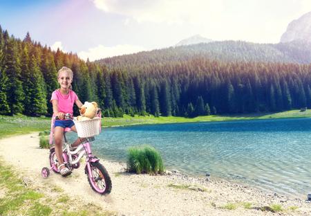 mignonne petite fille: Cute petite fille à vélo sur le vélo rose près du lac