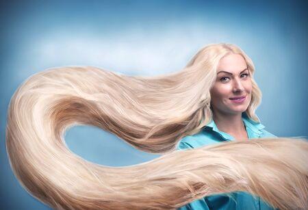 capelli lunghi: Giovane donna sorridente con lunghi capelli biondi Archivio Fotografico