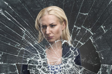 mirror: Depressed adult woman stands behind broken glass