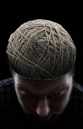 odd jobs: Young man with closed eyes and with balls of yarns instead of his brain Stock Photo