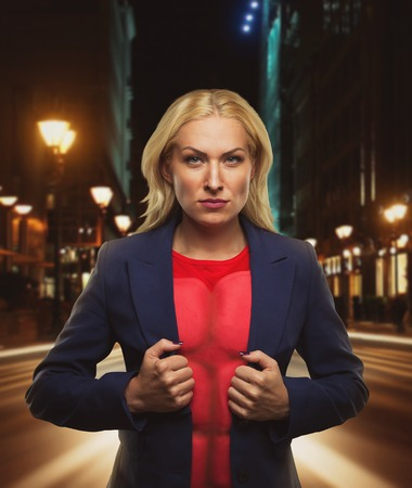 super hero: Strong woman superhero showing off her strength in night city street