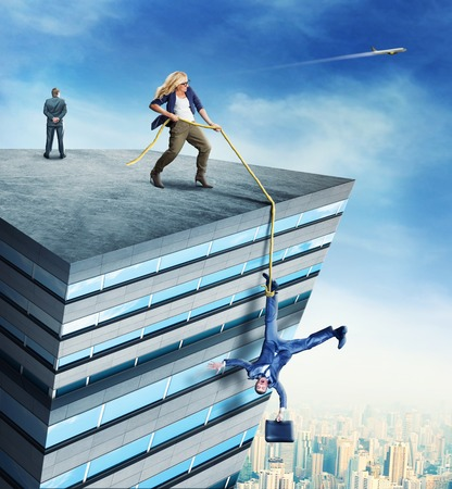 standing businessman: Woman standing on the roof a high building is rescueing a businessman with the rope