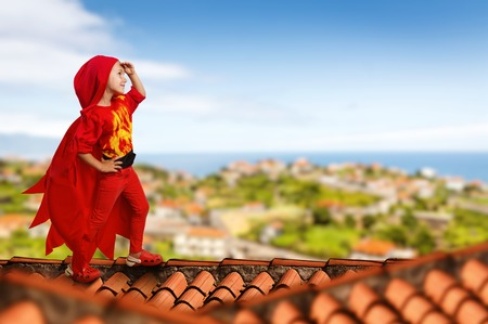 Little girl in a superhero costume standing on the roof Stock Photo