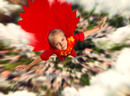 Little super hero girl in red costume is flying over the city