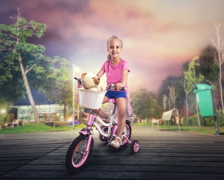 pink bike: Smiling little girl cycling on pink bike on the street in the night Stock Photo