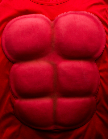 festival scales: Red artificial press muscle for superhero costume Stock Photo
