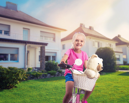 freetime activity: Smiling little girl cycling on pink bike on the street near the house