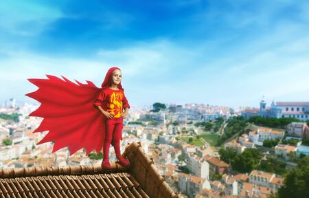 Little girl in a superhero costume standing on the roof against cityscape Stock Photo
