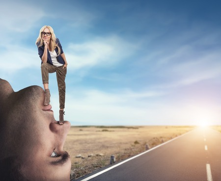 psych: Young confident woman standing on the mans face Stock Photo