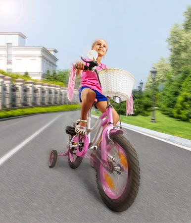 pink bike: Cute little girl is cycling on pink bike on the street