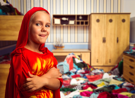 Little girl in masquerade costume in the room with heap of clothes