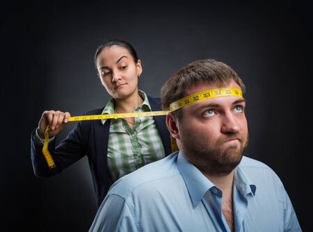 measuring: Businesswoman measuring mans head with metre-stick