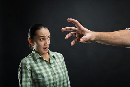 dominacion: Mujer joven asustado con la enorme mano del hombre sobre negro