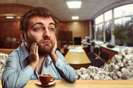odd jobs: Thoughtful businessman with a big head drinking coffee in the office Stock Photo