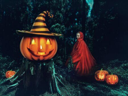 calabazas de halloween: Niña en un vestido rojo en el bosque con calabazas Helloween Foto de archivo