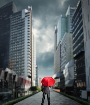 sotto la pioggia: Businessman standing back with a red umbrella in the city Archivio Fotografico