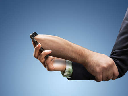 obsession: Businesswoman hand with a phone that holds it like a mans hand  - phone addiction concept