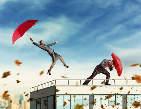 wind storm: Businesspeople with umbrellas on the skyscraper while storming Stock Photo