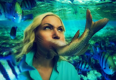 adult mermaid: Womans face smoothly changing to fishtail under the water