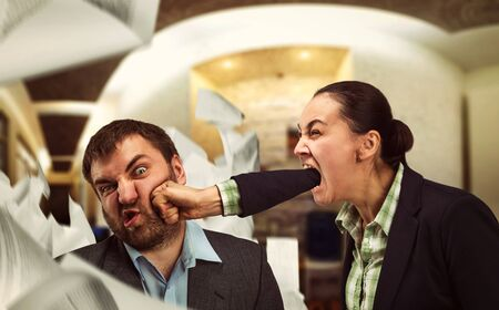Businesswoman shouts at young businessman and beats him
