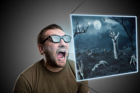 terrible: Scared man in 3D glasses looking at terrible picture