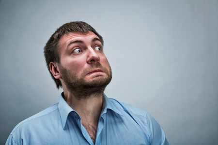 anguished: Frightened businessman wearing blue shirt over grey Stock Photo