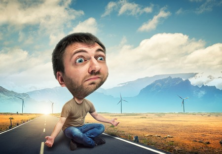 huge: Man with a big head sitting on the road Stock Photo