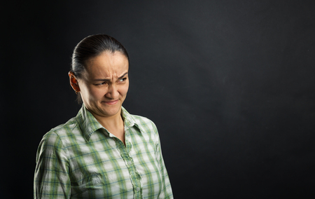 is disgusted: Disgusted woman standing over black background Stock Photo