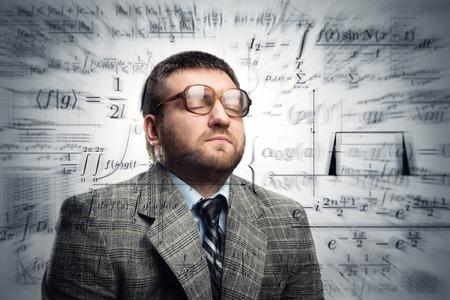 profesor: Profesor en vasos de pensar acerca de las fórmulas matemáticas Foto de archivo