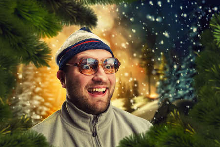 winter evening: Excited man in winter evening near firtrees Stock Photo