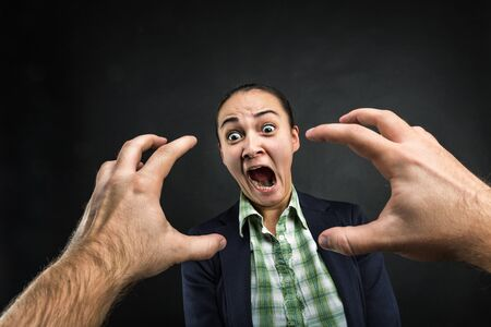 male face: Young woman frightened with huge human hands