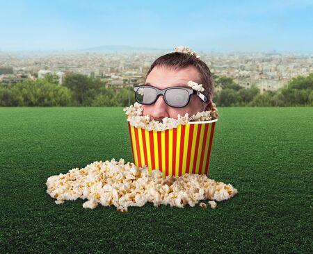 3d weird: Man in glasses in a bucket of popcorn in the meadow