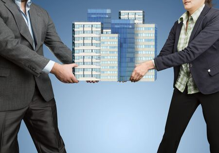 contend: Businesspeople holding in their hands big office buildings Stock Photo