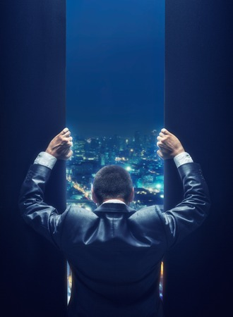 opportunity discovery: Businessman opening the gate to a night cityscape