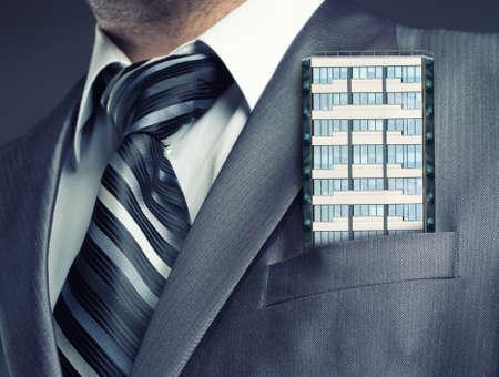 businessman suit: Businessman with office building in suit pocket