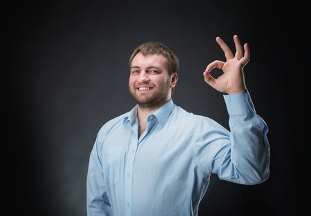 ok hand: Smiling man showing ok hand sign Stock Photo