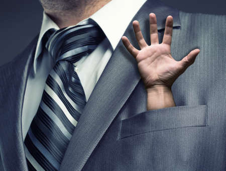 hand in pocket: Businessman with human hand in suit pocket Stock Photo