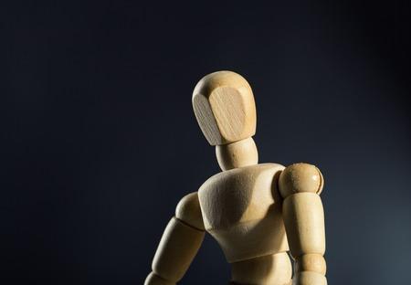 artists dummy: Sad human wood manikin against dark background