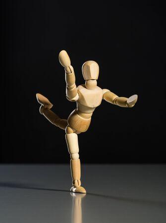 wooden mannequin: Human wood manikin dancing against dark background Stock Photo