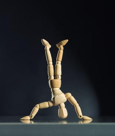 cabeza abajo: Maniquí de madera humana de pie boca abajo contra el fondo oscuro