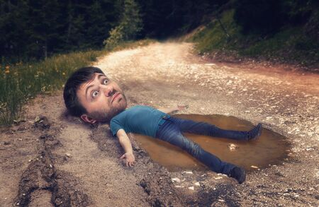 rut: Man with a huge head in the puddle on rut road after rain in forest
