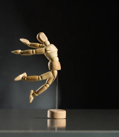 marioneta de madera: maniquí de madera humana está saltando contra el fondo oscuro