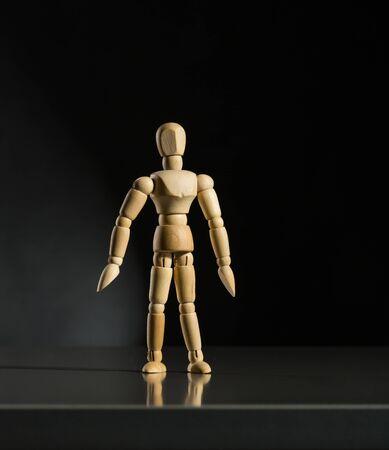 artists dummy: Human wood manikin is standing against dark background