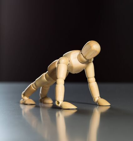 artists dummies: Human wood manikin is doing push-ups against dark background Stock Photo