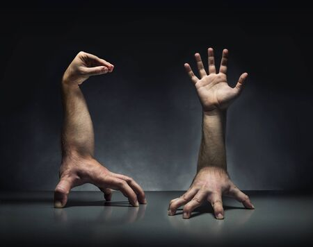 Strange human hand creatures on the grey table